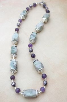 Sadly, I don't know what the big stones are...they are a lovely light green with purple and cream inclusions. They are rectangular and faceted and I have adorned them with square bead caps in silver plate. I combined the larger beads with Amethyst rounds and faceted iridescent Czech glass in purple, and silver glass seed beads The necklace is an asymmetrical design and finished with a silver tone toggle clasp.