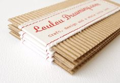 Amazing little business cards for Loulou Dreaming. Fabric, red thread, corrugated cardboard.