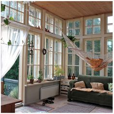 Dream porch with hammock, floor-to-ceiling windows, and paneled ceiling.
