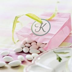 Personalized Bag with Almonds  Fill colorful paper bags with candy-coated almonds for wedding guests.  To personalize the gift, create a monogram tag using card stock, a punch and stickers.  Thread ribbon through a punched hole and tie around the top of the bag to keep it closed.