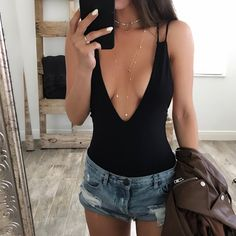 Deep V plunging neckline black bodysuit with double strap back. Model is wearing Small.