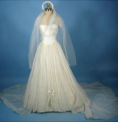 1950's Sheer Wedding Gown Complete with Original Attached Ruffled Underskirt, Original Satin Slip, Original Hoop Petticoat, Original Satin Twisted Headpiece with Wax Flowers and Veil, Original Sheer Gauntlet Gloves. at Antique Dress