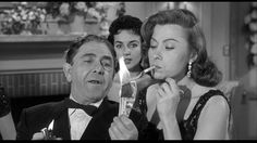 Moe Howard, Harriette Tarler (right) | Flying Saucer Daffy (1958), a Three Stooges short produced and directed by Jules White; distributed by Columbia Pictures | Tags: burning money, cigarette smoking, nouveau riche