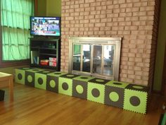 Baby proofing the fireplace with foam mats.