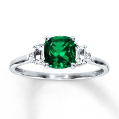 A cushion-cut lab-created emerald holds the spotlight in this elegant ring for her. Baguette lab-created white sapphires grace either side, with twin round diamonds providing the finishing sparkle. The ring is styled in 10K white gold.