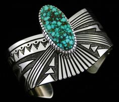 Alton Bedonie Gem Grade Turquoise Mountain Spiderweb Curved Overlay Bracelet #AltonBedonie #Cuff Using a large and exciting Turquoise Mountain gem, Alton floats the stone on the bracelet shank to emphasize the beauty of the specimen. It sits off the side of the shank in his signature high hand chiseled bezel. Blue green is the background color of the gem, with fine chocolate and golden-brown spiderwebbing in layers throughout.