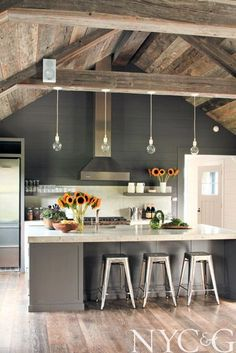 Gray and white, small lights, beams, rustic ceiling, alcove for stools - simple and chic design.