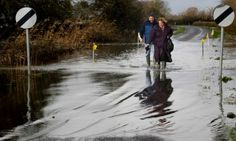 A couple approach flood water on the road at Burrow Bridge on January 28, 2014 in Somerset
