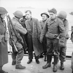 "British paratroopers search German POWs brought onboard a warship on the day of the Normandy landings, June 6, 1944. Note the para on the left; he has ""confiscated"" a German rifle and carries a Short Magazine Lee-Enfield Mk I (Model 1903). This is somewhat odd because the paras had already been issued with the No. 4 Mk by 1944."