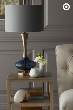 "Just because it's a ""side"" table doesn't mean it can't be the center of attention. Give it something modern and sophisticated, like this metallic lamp to stand out."