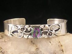 "A faceted mystic topaz gem is in this pretty silver cuff bracelet by Johnny Watson, Navajo. The gem is set in a four prong setting with rainbow colors with silver leaves, beads, swirls and flowers at the sides. The bracelet is 1/2"" wide with an inside measurement of 5 1/4"" and a 1"" opening. Adjustable. Fits approx. 6"" to 6 1/4"" wrist. Signed by the artist."