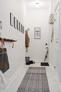 White walls in narrow hallways can really open it up; no windows make things difficult, but I like the way the light is white, so making it seem larger than it is. A shade would make it warmer, but it's pleasant as it is.