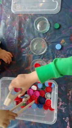 Farben sortieren mittels Zange und Flaschendeckeln