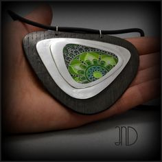 Sillver pendant decorated with green pattern made of enamel cloisonne. Pendant isframed in Bog Oak(Blac Oak) wood. www.facebook.com/ANDcli