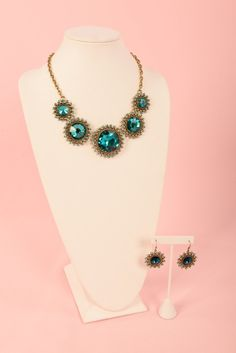 This piece has just the right amount of sparkle.  The Azalea necklace and earring set contains   large center green gemstones surrounded by smaller green gemstones set on a gold finish.  www.brillantezza.com