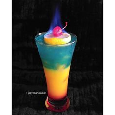 BOOZIECHIC'S BIRTHDAY COCKTAIL  1 oz (30ml) Grenadine 1 ½ oz (45ml) White Tequila 1 oz (30ml) Blue Curacao 3 oz Orange juice A drizzle of Bacardi 151 *Pour grenadine in your glass. Fill it with ice. Layer in orange juice. Layer in tequila and blue curacao mix. Take a slice of lemon sit it on top. Add cherry Drizzle Bacardi 151 on your lemon and cherry. Set on fire.