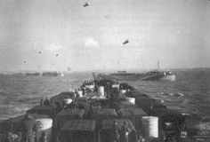 Looking from the bridge of HMS LST-427 toward 'Sword' beach during the Invasion of Normandy, 6 June 1944. HM LST-423 is just ahead of HM LST-427 off her starboard bow with other LSTs moving in column toward the beaches.