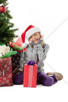smiling elementary girl with her christmas gift. - Smiling elementary girl with her christmas gift looking at camera while sitting near christmas tree, Model: Alyssa Power