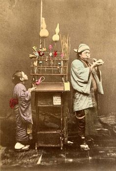 "Japanese confectioners 1897 ""The confections made from a paste are blown like glass into various shapes, and allowed to harden"", quoted from the 1897 caption. This studio shot is interesting: the poses are not standard, and the context they provide with their well-worn, everyday garments next to the beat-up portable ""Candy Store"" makes this image valuable for capturing a seldom seen moment of a Child's life in old Japan."
