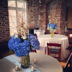 Centerpieces of Shocking Blue Hydrangeas, Curly Willow Branches, and Cotton Stalks