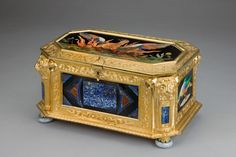 This is a jewel casket designed by  Samson Wertheimer, between 1811-92. It is made up of geometric designs and lapis lazuli, and is adorned with gold, as well as having a lot of floral scrollwork definition throughout it.