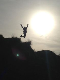 Person leaping in air at edge of cliff looking dunes. My cousin took this photo.