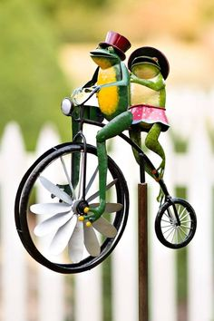 A pair of anachronistic amphibians are the stars of this handmade metal garden art. The spokes on the front wheels will spin in the wind and cause the legs to move up and down in a moving motion. A wonderfully imaginative garden decoration with a unique spin when the wind blows.