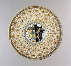 Plate with ridge on rim; earthenware covered front and back with presumed tin glaze; painted decoration on front (with red). In centre a shield of arms, doubtfully identified as Cesi impaling Belluomi: (a) lustre on a mount white a tree green; in chief a label red of four points, three fleur-de-lis blue-black between the points; (b) blue a lion rampant lustre. On rim, stylised rosettes in panels divided by radiating, concentric blue lines.
