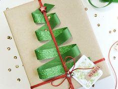 Weihnachtsgeschenk verpacken und mit einer grünen Schleife mit rotem Stern verzieren