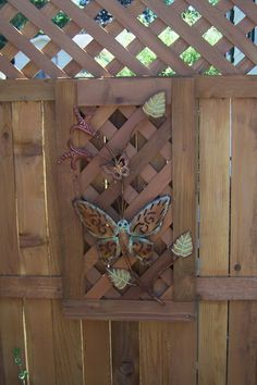Fence Art. Metal art is from Hobby Lobby applied to a lattice frame made from leftover fencing. Hung with two screws and copper wiring to two screws on the fence. Made portable so it can be removed for the winter.