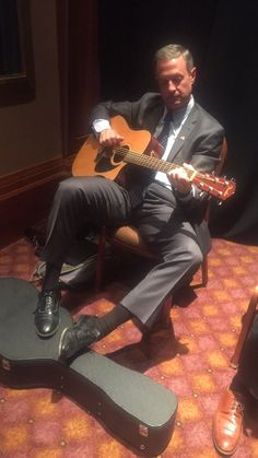 Martin O'Malley sitting and playing guitar