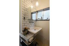 洗面室はすっきりと白のタイルで。アンティークのミラーでラフさが出ています。