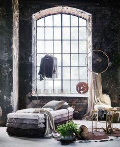 Et stort vindue i industriel stil omgivet af bløde elementer i form af tæpper, masser af plaider og en sofa lavet af madrasser.