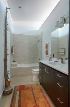 This splendid bathroom uses a variety of colorful accents to great affect . Dark wooden cabinetry, white basin, large driftwood, pottery add specialty to this bathroom.