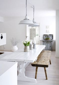 Crisp White Scandinavian Home. White painted farm table. rustic bench. all white dining area. White metal pendant lights.