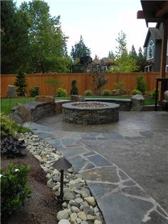 Could do something like this in back corner near apple tree. Make bench area a wall for the raised veggie beds? Then set lounge chairs on other side of firepit?   Concrete Patio  Sublime Garden Design  Snohomish, WA