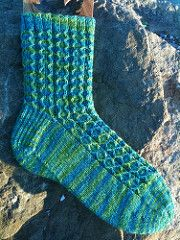 "This sock was designed for Sock Madness 5. It features a traveling slip stitch pattern that works well with variegated, semi-solid, or solid yarns. It has a heel flap with a ""riverbed"" gusset and a star toe."