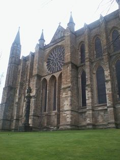 """ENGLISH ROMANESQUE: Back of Durham Cathedral. Here we also see an early appearance of a """"rose"""" window. The pointed arches also hint at the Gothic style but note the heavy buttresses supporting the weight of the walls. This is still a Romanesque structure."""