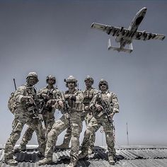 TACP team posing in Afghanistan with their battle buddy the A-10 while standing on their B-huts.