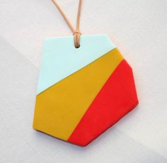 This vibrantly coloured geometric pendant is made from polymer clay. It is backed with a layer of the red colour and hangs from polished cotton cord