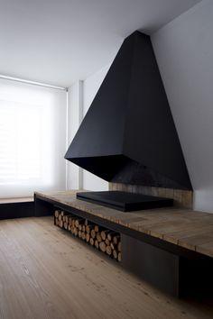 Matte black smoke hood for flat surface fireplace. Wood storage underneath.