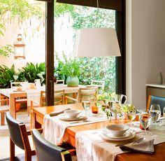 Comedor con salida al patio, con mesa de madera y sillas en madera y piel negra, lámpara de techo, caminos de mesa