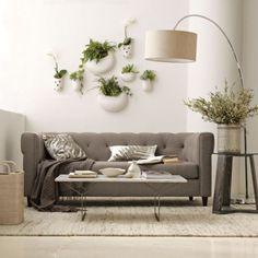 Des pots de fleurs suspendus en céramique pour une ambiance végétale. J'adore ce mélange gris et tons neutres avec la végétation.