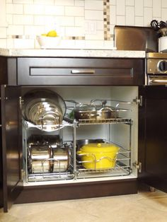 A shelf system that slides out lets you easily pick up (and store) awkward items like heavy pots and pans.   See more at Mini Manor Blog »