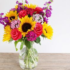 Meet the Vibrant Summer bouquet; arrangement of sunflowers sweet Williams scented purple stocks and cerise roses.
