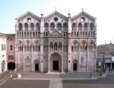 """Facciata della cattedrale di Ferrara, dedicata ai Santi Giorgio e Maurelio. La sua costruzione fu iniziata nel XII secolo in stile Romanico ma successivamente subì influenze Gotiche, come si può notare dell'elegante loggia. Nella parte inferiore, sopra la porta centrale sono rappresentare, in stile Romanico, scene dall'Antico Testamento. Invece in quella superiore appaiono le arcatelle e i finestroni strombati tipici del Gotico e un """"giudizio universale"""" scolpito da un artista ignoto."""