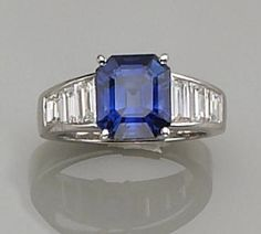 A sapphire and diamond ring  centering a rectangular-cut sapphire, flanked by graduated baguette-cut diamonds on a plain mount; estimated total sapphire weight: 4.70 carats; estimated total diamond weight: 1.80 carats; mounted in platinum.