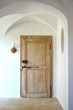 Antique heavy wood doors for indoor doors to make hallway feel outdoors, white plaster walls