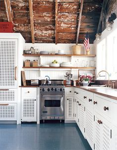 In this Nantucket kitchen designed by Gary McBournie, the simple plank floor is painted Benjamin Moore's Deep Ocean and spattered in red, white, and blue. Cabinetry by local furniture maker Carter Mitchell. Sconces are brass marine fixtures. Teak countertops.