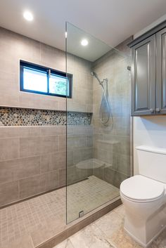 Underlit his and hers vanity with stone countertop and frameless mirrors. Recessed can lights above sink and shower area for even lighting perfect for aging in place. Walk-in shower with tiled niche and removable shower head and tile-in shower drain.